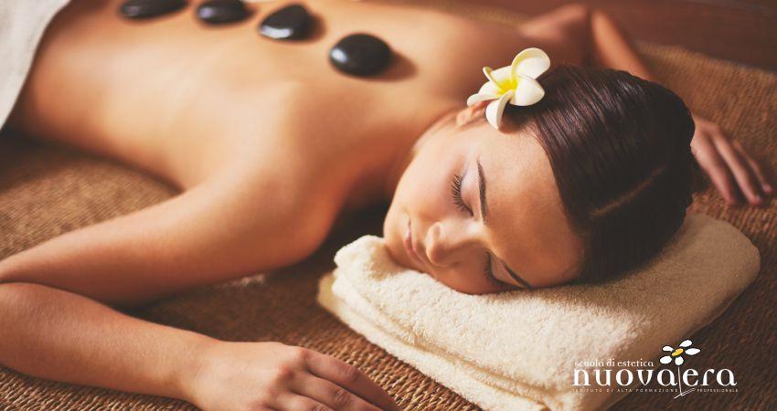 Donna a spalle nude stesa su lettino con fiore bianco sull'orecchio e ciottoli neri sulla schiena