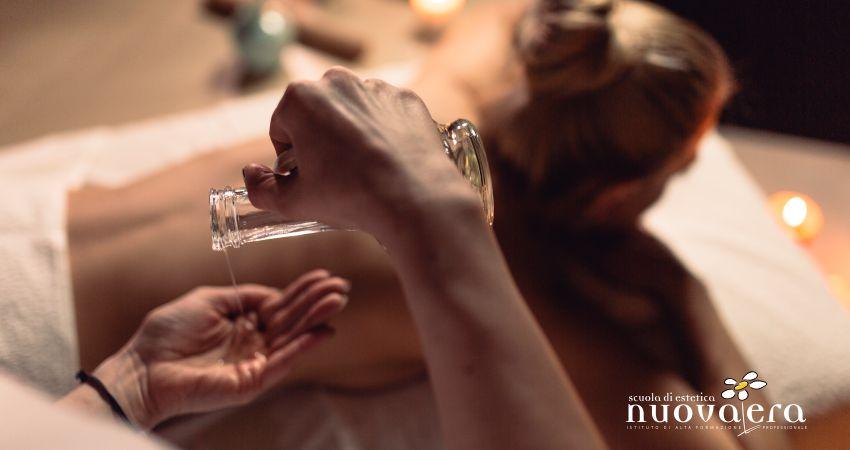 Mani di donna versano olio per massaggi da boccetta con donna stesa su lettino sullo sfondo