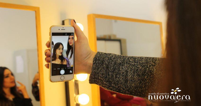 Mano di ragazza regge uno smartphone acceso con un suo selfie insieme ad un'amica