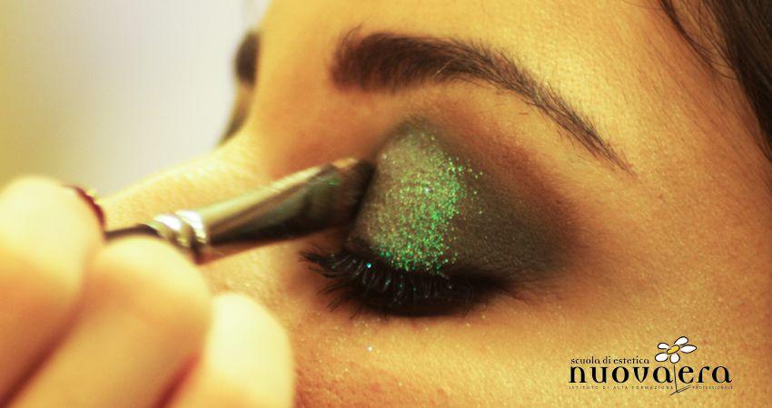 Primo di pennello da Make-Up che spalma ombretto verde glitterato su una palpebra femminile