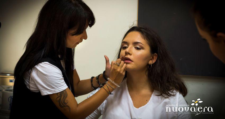 Una docente mostra l'applicazione del rossetto nero sulle labbra di un'alunna
