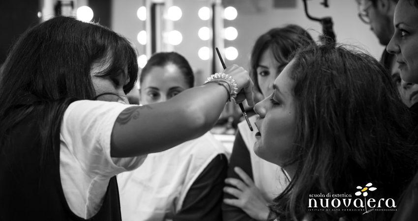 Foto in bianco e nero di una docente mostra l'applicazione del rossetto nero sulle labbra di un'alunna