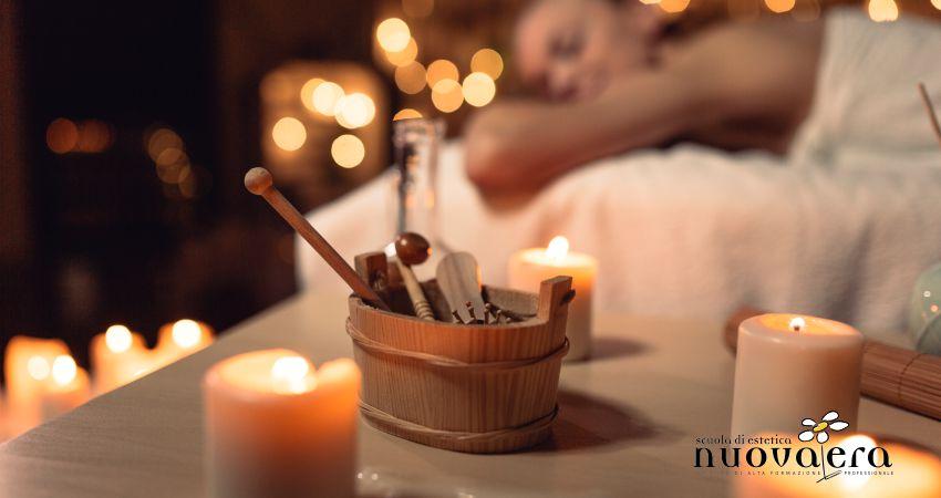 Secchiello in legno contenente strumenti per i massaggi accanto a candele accese con donna stesa su lettino sullo sfondo