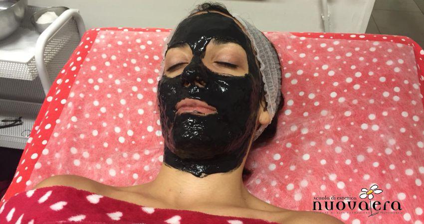 Ragazza stesa su lettino con maschera di bellezza nera applicata sul viso
