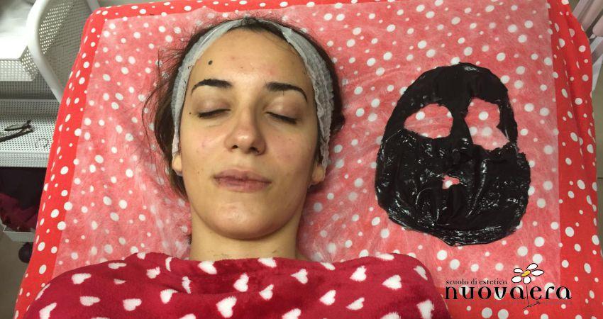 Ragazza stesa su lettino ad occhi chiusi accanto a maschera di bellezza nera